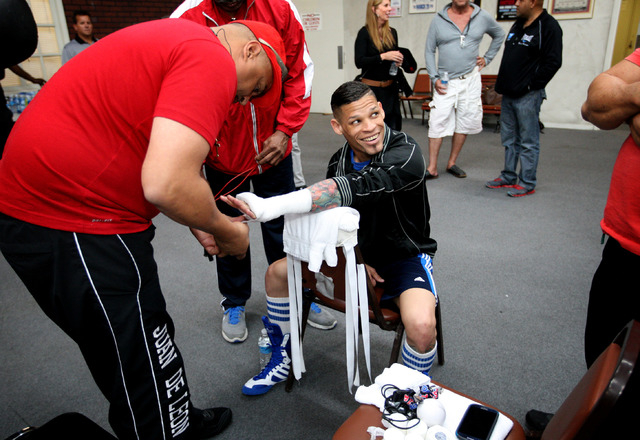 Featherweight boxer Orlando Cruz, center, has his hand taped before working out at the Top Rank Gym in Las Vegas on Monday.  (Jessica Ebelhar/Las Vegas Review-Journal)