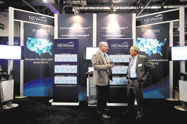 Jim Bach, co-founder of Las Vegas-based NEWave Inc., left, talks with convention attendee Bruce Zweber of Minneapolis at the NEWave booth at the G2E convention in Las Vegas Tuesday, Sep. 24, 2013. ...