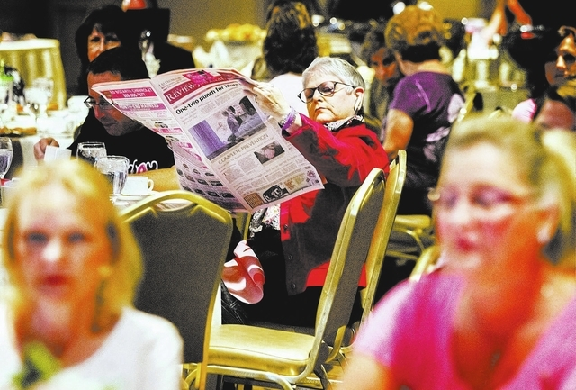 Leslee Rogers reads the Las Vegas Review Journal newspaper during Pink Paper Day Celebrity Breakfast at the Suncoast hotel-casino on Wednesday. The event, sponsored by the Las Vegas Review-Journal ...