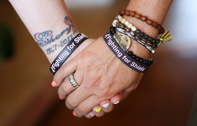 Morgan Burns, left, and her mother Shiela  hold hands and wear matching breast cancer support bracelets as well as memorial tattoos on their inner left wrists.  Shiela was recently treated for bre ...