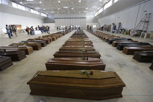 Coffins of the dead migrants are lined up inside an hangar of Lampedusa's airport, Italy, Saturday, Oct. 5, 2013.  A ship carrying African migrants towards Italy sank Thursday after a fire was set ...