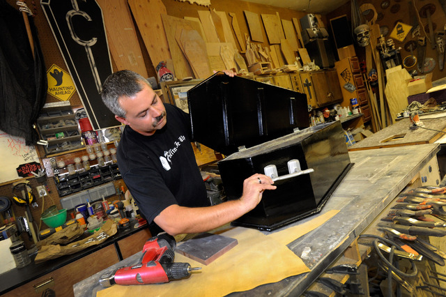 Bryan Schoening demonstrates a coffin-shaped cooler in his workshop. In 2000, his daughter Destiny asked him to make a coffin for Halloween. Schoening says the challenge addicted him to building c ...