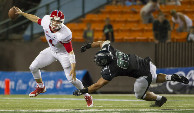 Fresno State quarterback Derek Carr, left, manages to escape from Hawaii defensive lineman Beau Yap in a football game on Sept. 28 in Honolulu. Fresno State defeated Hawaii 42-37. (AP Photo/Eugene ...