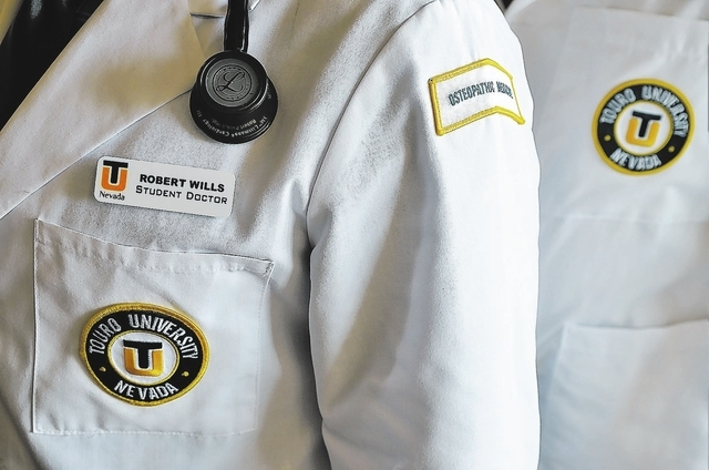 The white coats worn by second-year medical student Rob Wills, left, and Dr.Ronald Hedger, assistant dean of clinical skills training at the Touro University Nevada College of Ostropathic Medicine ...