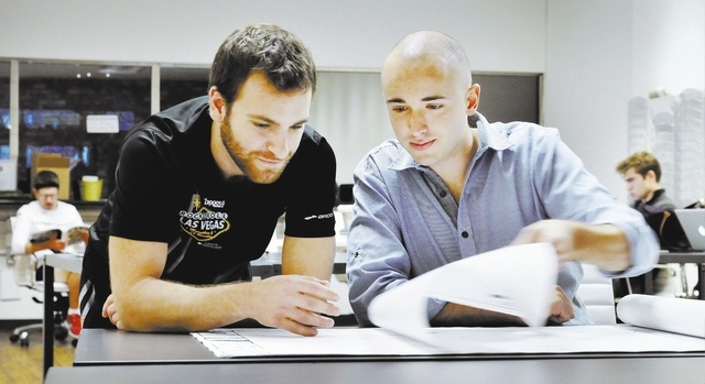 Venture for America fellows Josh Levine, left, and Jude Stanion look over plans in the Downtown Project co-working space at 515 Fremont St. in Las Vegas on Sunday, Dec. 2, 2012. The program pairs  ...