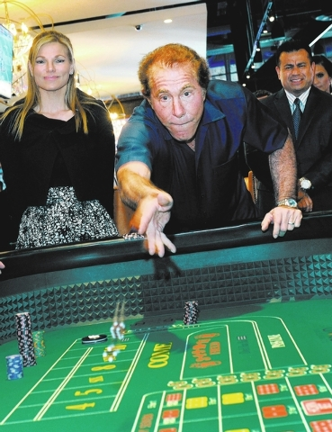 Steve Wynn, center, throws out the dice after placing a bet on the opening day of the Downtown Grand Las Vegas hotel-casino on Sunday, Oct. 27, 2013. Wynn's wife, Andrea Wynn, left and Ricardo Ram ...