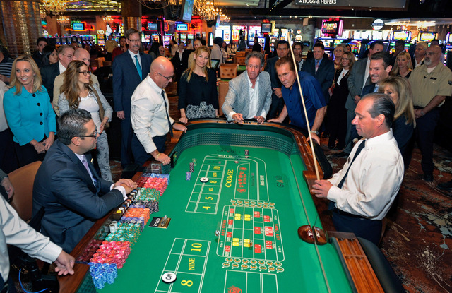 Retired casino executive Marc Schorr, center, and the father of Seth Schorr, CEO of the Downtown Grand Las Vegas tosses the dice during opening day at the Downtown Grand Las Vegas hotel-casino on  ...