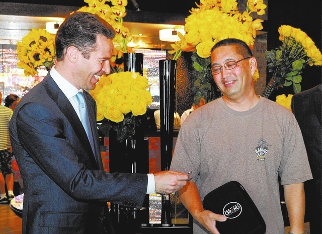 Seth Schorr, left, CEO of the Downtown Grand Las Vegas  gives Alan Oshiro a $100. gaming chip as a token for being the first person to check into the now open Downtown Grand Las Vegas hotel-casino ...