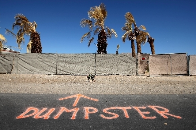 """Flowers and a spray-painted sign reading """"DUMPSTER"""" are seen at the scene where a man was found dead inside a dumpster on Ringe Lane near the intersection of Nellis Boulevard and Owens Avenue. ( ..."""
