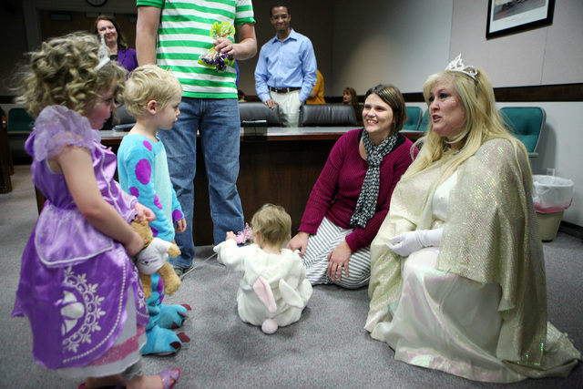 Sasha, 4, left to right, Skyler, 3, Sydney, 1, and their mother Bethany Overland share a moment with District Court Family Judge Cynthia Giuliani, right, after Sydney's adoption hearing Thursday,  ...