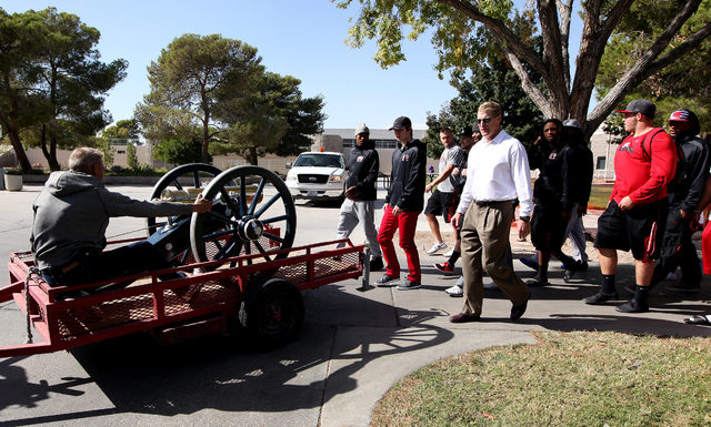 Members of the UNLV football team follow the Fremont Cannon as it makes its way through the UNLV campus in Las Vegas on Monday.(Justin Yurkanin/Las Vegas Review-Journal)