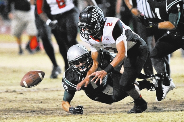 Las Vegas Jacob Littlefield (2) fights to recover a fumble by Green Valley's Kyler Chavez (13) during a football game at Green Valley High School in Henderson, Nev. Friday, Oct. 11, 2013. (David C ...
