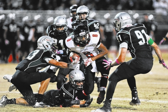 Las Vegas running back Corey Sinceno (8) is brought down by a host of Green Valley defenders including Albert Lake (23) and Derrick Webb (91) during a football game at Green Valley High School in  ...
