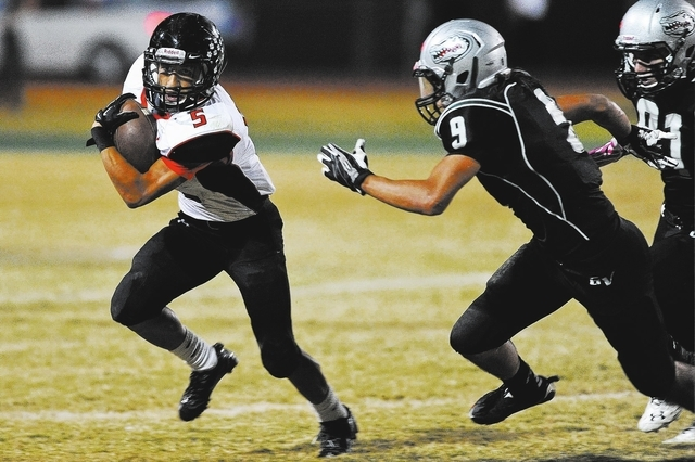 Las Vegas back Andrew Moreland (5) looks for running room against Green Valley's Jairo Rebolledo (9) during a football game at Green Valley High School in Henderson, Nev. Friday, Oct. 11, 2013. (D ...