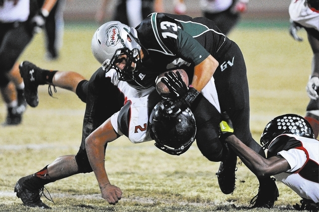 Green Valley's Kyler Chavez (13) is tackled by Las Vegas defender Jacob Littlefield (2) during a football game at Green Valley High School in Henderson, Nev. Friday, Oct. 11, 2013. (David Clevelan ...