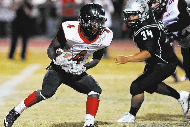 Las Vegas running back Elias Miller (4) looks for running room in front of Green Valley's Blaze Brooks (34) during a football game at Green Valley High School in Henderson, Nev. Friday, Oct. 11, 2 ...