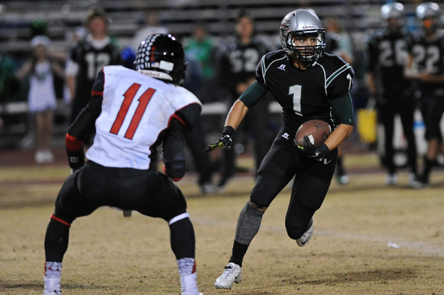 Green Valley's Giovanni Hernandez (1) looks for running room against Las Vegas defender Aaron Zanin-Banks (11) during a football game at Green Valley High School in Henderson, Nev. Friday, Oct. 11 ...