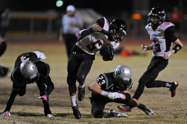Las Vegas running back Andrew Moreland (5) regains his balance between Green Valley's Jacob Tomlin (3) and Albert Lake (23) during a football game at Green Valley High School in Henderson, Nev. Fr ...