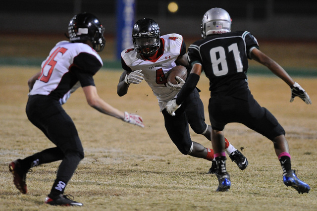 Las Vegas running back Elias Miller (4) looks for running room against Green Valley's Kyle Parker (81) during a football game at Green Valley High School in Henderson, Nev. Friday, Oct. 11, 2013.  ...