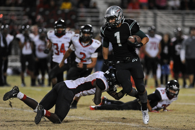 Green Valley's Giovanni Hernandez (1) breaks an attempted tackle by Las Vegas defender Elias Miller (4) during a football game at Green Valley High School in Henderson, Nev. Friday, Oct. 11, 2013. ...