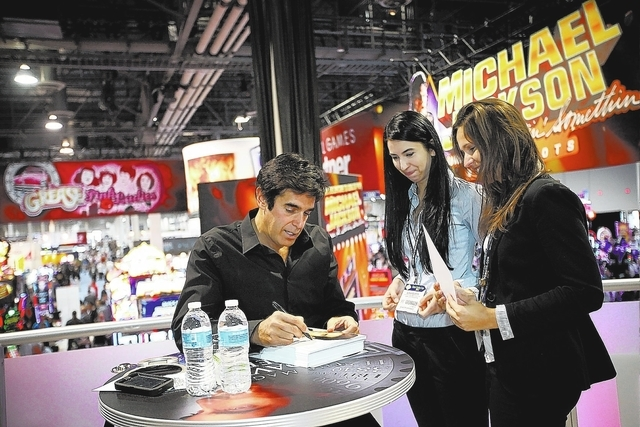Magician David Copperfield, left, signs autographs for Polish visitors Blanka Seweryn, center, and Marzena Zaziabl at the G2E convention in Las Vegas Tuesday, Sep. 24, 2013. (Jessica Ebelhar/Las V ...