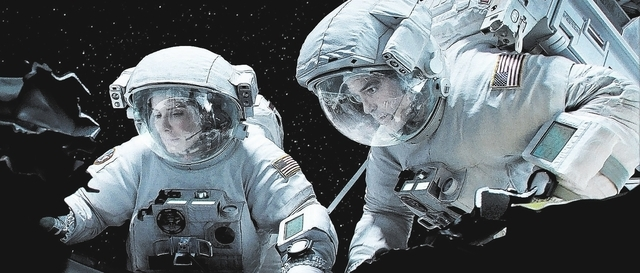 "SANDRA BULLOCK as Ryan Stone and GEORGE CLOONEY as Matt Kowalski in Warner Bros. Pictures' dramatic thriller ""GRAVITY,"" a Warner Bros. Pictures release.  Photo courtesy of Warner Bros. Pictures"