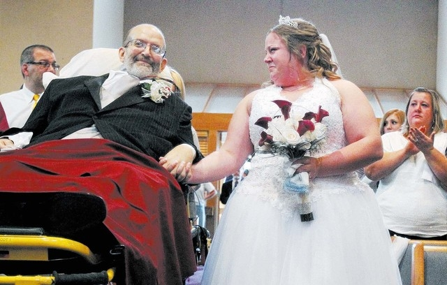 Bride Sarah Nagy, right, begins to cry as she is escorted by her father, Scott, down the aisle during her wedding ceremony Oct. 12, 2013 at First Lutheran Church in Strongsville. University Hospit ...