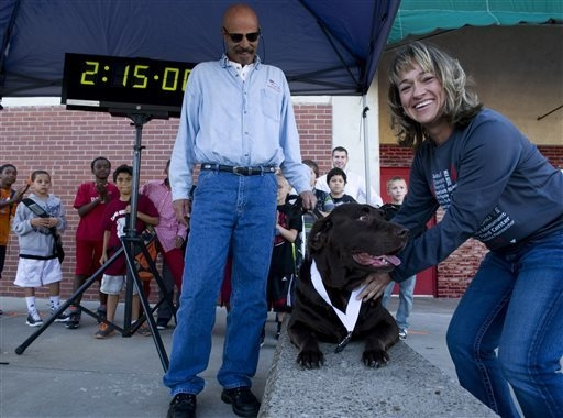 Kim Arney of Evansville, right, poses with Boogie, an 8-year-old chocolate Labrador owned by Jerry Butts, center, outside the Downtown YMCA after awarding him his medal Monday, Oct. 7, 2013, for f ...