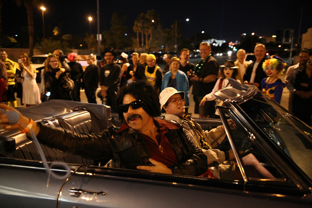 A man dressed as Hunter S. Thompson, right, with a man dressed as his lawyer drive down Fremont Street during the Las Vegas Halloween Parade near downtown Las Vegas on Thursday, Oct. 31, 2013. (Ch ...