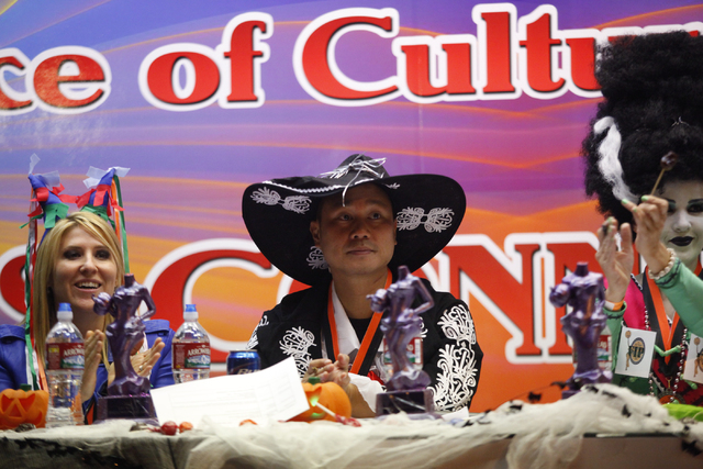 Zappos CEO Tony Hsieh, center, helps judge costumes and floats during the Las Vegas Halloween Parade as it goes down Fremont Street in downtown Las Vegas on Thursday, Oct. 31, 2013. (Chase Stevens ...