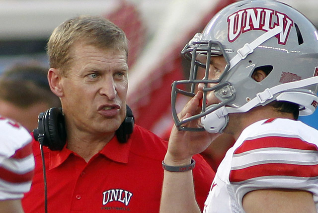 UNLV head coach Bobby Hauck, left, talks to a player on the sideline during the second quarter against Minnesota of an NCAA college football game, Thursday, Aug. 29, 2013, in Minneapolis. (AP Phot ...