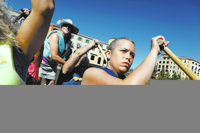 Holly Lyman, back standing, steers as Anna Friday, front right, paddles during a Pink Paddlers team practice at Lake Las Vegas on Sept. 22. The team, made up of breast cancer survivors, plans to c ...