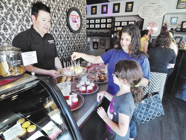 Showboy BakeShop co-owner Jared Sullivan offers complimentary cake pops to Tammy Shapiro and her daughter Samantha. (Bill Hughes/View)
