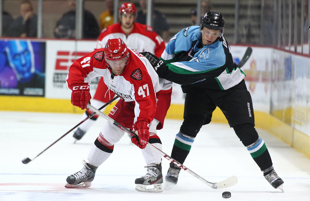 Las Vegas Wranglers' Cody Purves, left, battles for the puck against Alaska Aces' Zach Davies during a game at the Orleans Arena in Las Vegas on Friday, Oct. 25, 2013. (Chase Stevens/Las Vegas Rev ...