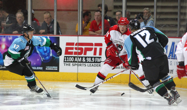 Las Vegas Wranglers' Geoff Irwin, center, looks to get past Alaska Aces' Jordan Kremyr during a game at the Orleans Arena in Las Vegas on Friday, Oct. 25, 2013. (Chase Stevens/Las Vegas Review-Jou ...