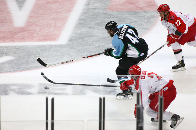 Las Vegas Wranglers' Greg Coburn (21) goes for the puck against Alaska Aces' Nick Mazzolini during a game at the Orleans Arena in Las Vegas on Friday, Oct. 25, 2013. (Chase Stevens/Las Vegas Revie ...
