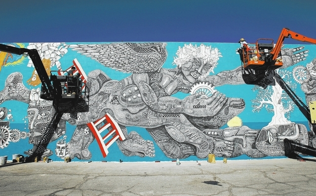 Cody Chapman, left, helps Zio Ziegler, right, paint a mural in downtown Las Vegas on Thursday. The mural is one of many painted for the Life Is Beautiful festival scheduled for this weekend.  (Joh ...