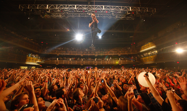 Imagine Dragons frontman Dan Reynolds swings over the crowd at the band's February show at the Hard Rock Hotel. Imagine Dragons is a top-billed act at the Life is Beautiful music and arts festiv ...