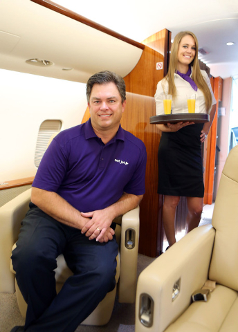 Set Jet CEO Tom Smith, left, sits inside a company CRJ 200 jet at Signature Flight Station Thursday, Oct. 10, 2013, in Las Vegas. Cabin hostess Candice Kading stands nearby. Set Jet, which is base ...