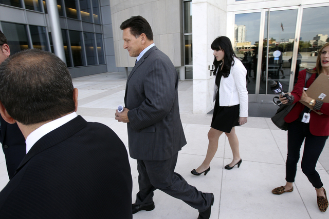 Longtime Family Court Judge Steven Jones, center, declines to talk to the news media Thursday, Nov. 1, 2012, outside the Lloyd George Federal Courthouse in Las Vegas after pleading not guilty to a ...