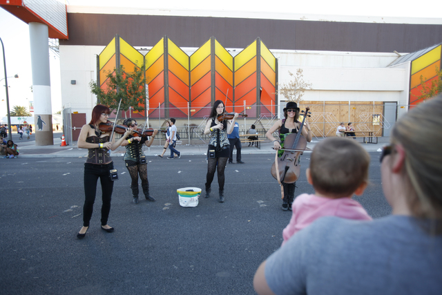 Amanda Maser, with 1-year-old Petra Blanco, watch street performers during the Life is Beautiful festival in downtown Las Vegas on Sunday, Oct. 27, 2013. (Chase Stevens/Las Vegas Review-Journal)