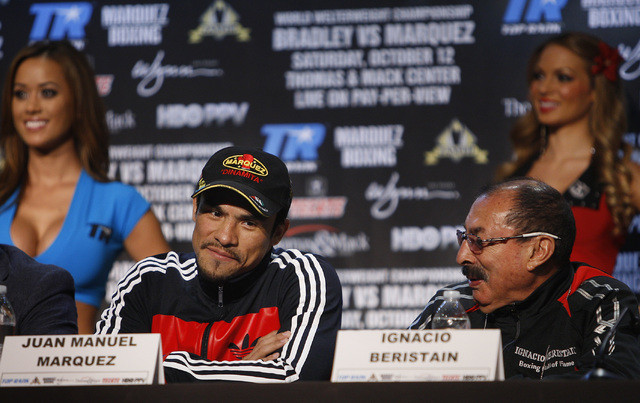 Boxer Juan Manuel Marquez, left, listens to his trainer Ignacio Beristain during the pre-fight press conference for his fight against Timothy Bradley at the Wynn Las Vegas on Oct. 9, 2013. (Jason  ...