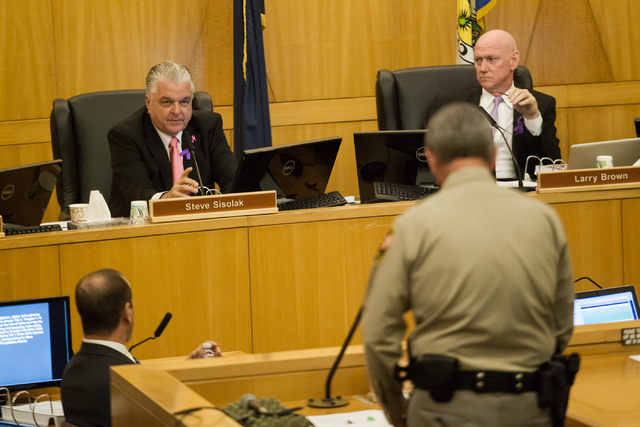 Clark County commissioner Steve Sisolak, left, addresses Clark County Sheriff Doug Gillespie during a hearing Tuesday on two proposals to raise the sales tax to pay for more police officers. (Chas ...