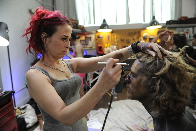 "Kelly ""Red"" Belmonte, star of the new reality show ""Naked Vegas"" on the Syfy channel, paints ""zombie groom's"" Dan Madonia's face. (David Becker/Syfy)"