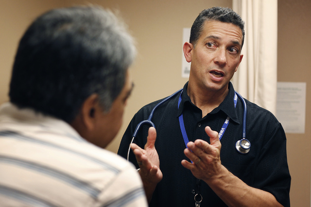 Dr. S. William Pierce, right, consults with patient Manuel Cisneros at the Volunteers in Medicine of Southern Nevada clinic in Las Vegas on Oct. 2, 2013. (Jason Bean/Las Vegas Review-Journal)