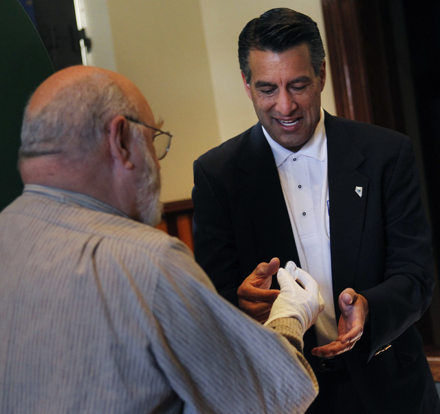Chief Coiner Ken Hopple, left, hands Governor Brian Sandoval the first pressing of the official State of Nevada sesquicentennial medallion during a minting ceremony at the Nevada State Museum in C ...