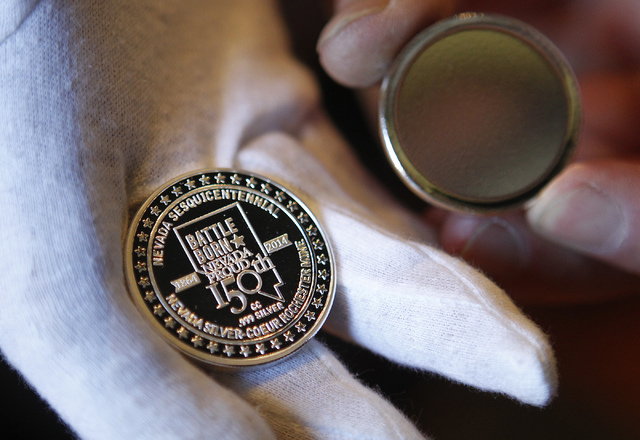 Chief Coiner Ken Hopple holds the first pressing of the official State of Nevada sesquicentennial medallion during a minting ceremony at the Nevada State Museum in Carson City on Oct. 25, 2013. Th ...