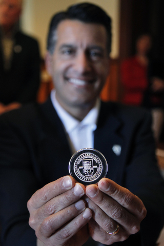 Governor Brian Sandoval holds the first pressing of the official State of Nevada sesquicentennial medallion during a minting ceremony at the Nevada State Museum in Carson City on Oct. 25, 2013. Th ...