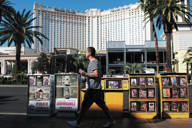 A man walks by news racks along Las Vegas Boulevard in Las Vegas, Tuesday, Oct. 22, 2013. An ordinance is being considered by Clark County that would ban all news racks on the Strip. (Erik Verduzc ...