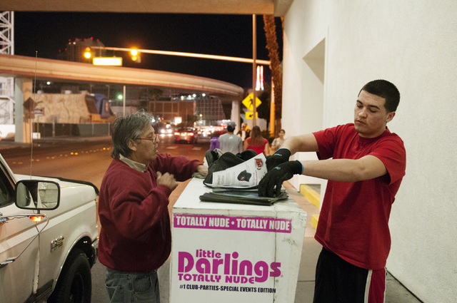 Eddie Munoz, left, owner of Strip Advertising, refills news racks with his son Brandon near Circus Circus Hotel in Las Vegas, Thursday, Oct. 24, 2013. An ordinance is being considered by Clark Cou ...